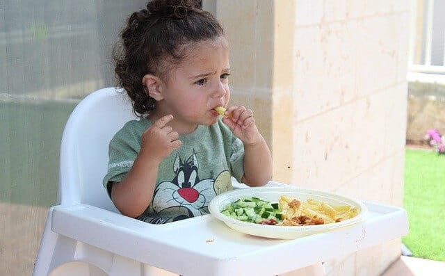 a child in a high chair eating more vegetables