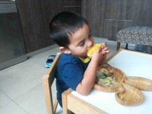 A boy seated in a table eating corn with other vegetables on his plate.