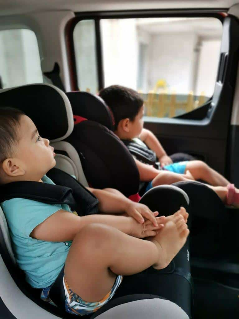 toddlers in the backseat ready for a long car drive.