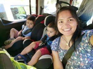 A mother sitting in the backseat with toddlers during a long car drive.